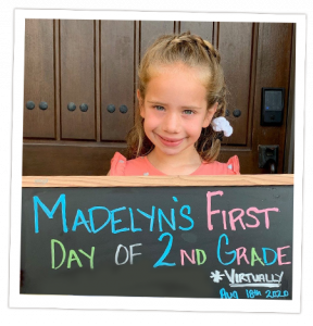 Transplant recipient, Madelyn, holding a chalkboard commemorating her first day of 2nd grade