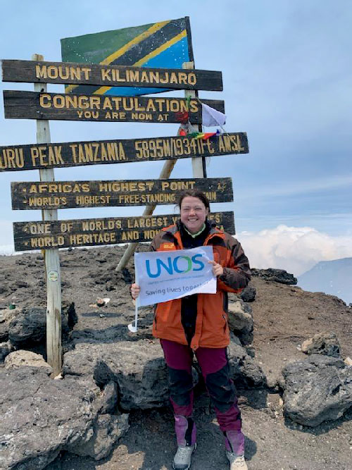 Alaina standing in front of Mt Kilimanjaro summit sign holding a UNOS sign