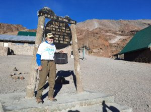Ski standing in front of Mt Kilimanjaro sign for Kibu Hut