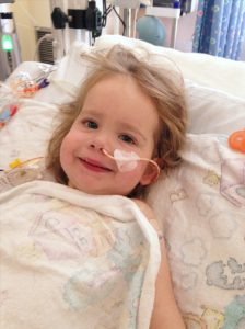 Heart recipient, Madelyn, smiling in hospital bed
